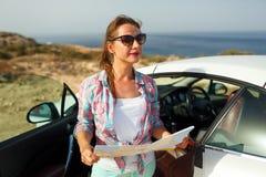 De jonge mooie vrouw ziet de kaart dichtbij cabriolet royalty-vrije stock foto's