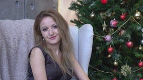 De jonge mooie vrouw zit in een ruimte met een Kerstboom op de achtergrond en bekijkt camera stock video
