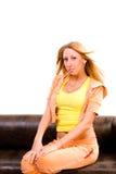 De jonge mooie vrouw zit op bank royalty-vrije stock foto's