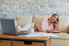De jonge mooie vrouw zit op een bank op een witte bakstenen muurachtergrond met een kop van koffie Laptop, documenten royalty-vrije stock foto