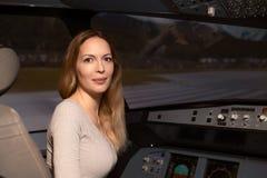 De jonge mooie vrouw zit op de zetel van de loods in de zetel bij het roer en het dashboard van een lijnvliegtuigvliegtuig stock fotografie