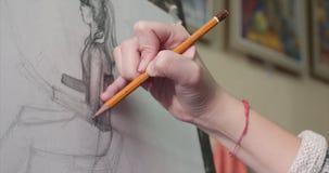 De jonge Mooie Vrouwelijke Kunstenaar is in Art Studio die, die achter een Schildersezel zitten en op Canvas schilderen Tekenings stock video