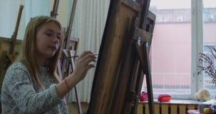 De jonge Mooie Vrouwelijke Kunstenaar is in Art Studio die, die achter een Schildersezel zitten en op Canvas schilderen Tekenings stock footage