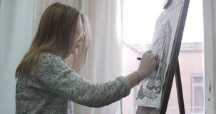 De jonge Mooie Vrouwelijke Kunstenaar is in Art Studio die, die achter een Schildersezel zitten en op Canvas schilderen Tekenings stock videobeelden