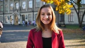 De jonge mooie vrouwelijke student toont duimen, gelukkig en positief, zijnd buiten de universiteit in een zonnige dag stock footage