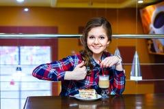 De jonge mooie vrouwen toont als aan kop van mokachino en cake Stock Foto's