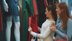 De jonge mooie vrouwen in de wekelijkse kledingsmarkt zijn de beste vrienden stock videobeelden