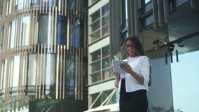 De jonge mooie vrouwenadvocaat gebruikt tablet, die zich op achtergrond van de bureaubouw bevinden stock footage