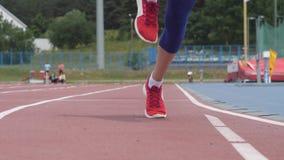 De jonge mooie vrouwenatleet begint bij atletiekspoor tijdens een dag opleiding in langzame motie4k video op UHD te lopen stock footage