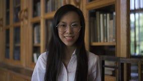 De jonge mooie vrouwenbioloog stelt in goede stemming die zich in bibliotheek bevinden stock videobeelden