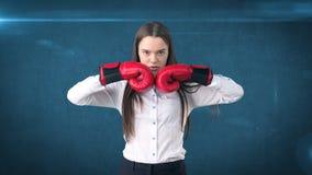 De jonge mooie vrouwenkleding in wit overhemd die zich in gevecht bevinden stelt met rode bokshandschoenen Bedrijfs concept Royalty-vrije Stock Afbeelding