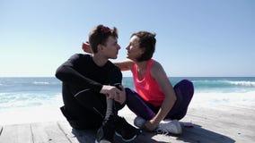 De jonge mooie vrouwenkussen passen de sportieve mens in de wang dichtbij de oceaan stock video