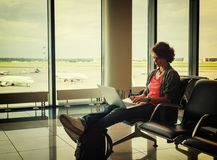 De jonge mooie vrouwenreiziger zit bij de luchthaven met laptop stock foto's