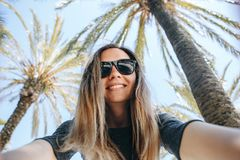 De jonge mooie vrouwentoerist of blogger maakt een selfie of rapporteert aan zijn abonnees over de achtergrond van palm royalty-vrije stock afbeeldingen