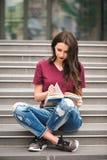 De jonge mooie vrouwenzitting en de lezing een boek genieten van van rust royalty-vrije stock afbeeldingen