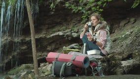 De jonge mooie zitting van de vrouwentoerist op halt in bos Mooi donkerbruin toeristenmeisje zit in het bos dichtbij haar rood stock videobeelden