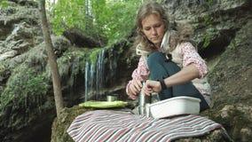 De jonge mooie zitting van de vrouwentoerist op halt in bos Mooi donkerbruin toeristenmeisje zit in het bos dichtbij haar rood stock footage