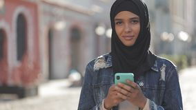 De jonge moslimvrouw die hijab headscarf tribunes in het stadscentrum dragen gebruikt haar telefoon en kijkt net aan de camera stock videobeelden