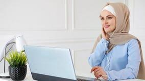 De jonge moslimvrouw is het luisteren muziek in oortelefoons gebruikend laptop en genietend van het stock fotografie