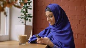 De jonge moslimvrouw in hijab met het doordrongen neus gebruiken telefoneert en het glimlachen bij camera, zittend in moderne kof stock footage