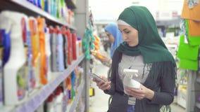 De jonge moslimvrouw in hijab in de supermarkt gebruikt de telefoon stock videobeelden