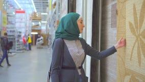 De jonge moslimvrouw kiest een tapijt stock video