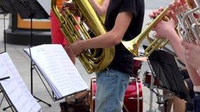 De jonge musicigroep voert muziek met blaasinstrumenten van nota's uit stock footage