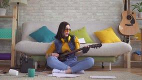 De jonge musicus die van de vrouwentuimelschakelaar emotioneel elektrische gitaarzitting op de vloer spelen stock footage