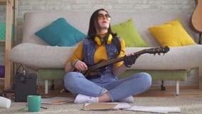 De jonge musicus van de vrouwentuimelschakelaar schrijft muziek op elektrische gitaarzitting op de vloer stock video