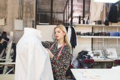 De jonge naaister draagt kleren op een model Een mooi meisje creeert kleren in een manierstudio royalty-vrije stock foto's