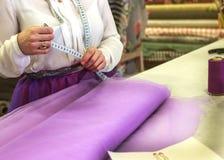 De jonge naaister maakt kleren snijdend stof Kleermaker met een naald De naaister maakt een meting royalty-vrije stock foto