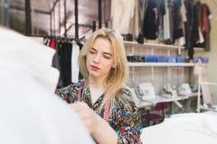 De jonge naaistervrouw bevindt zich in een studio dichtbij een manicure met kleren en de werken Het creëren van modieuze kleren stock foto's