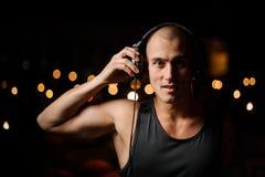De jonge nachtclub DJ in hoofdtelefoons voelt de muziek stock afbeelding