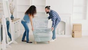 De jonge nieuwe flat van het paar bewegende meubilair stock footage