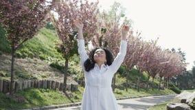 De jonge onbezorgde vrouw die witte lange kleding dragen geniet van van bloeiende sakurabomen stock videobeelden