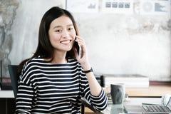 De jonge onderneemster die van Azië slimme telefoon spreken bij bureau met Stock Foto