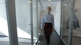 De jonge onderneemster gaat door de gang in modern helder bureau stock videobeelden