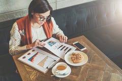 De jonge onderneemster in glazen en witte sweater zit in koffie bij lijst, het werken De onderneemster bekijkt grafieken royalty-vrije stock afbeeldingen