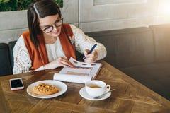 De jonge onderneemster in glazen en witte sweater zit in koffie bij lijst, het werken Het meisje bekijkt grafieken, grafieken stock afbeeldingen