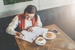 De jonge onderneemster in glazen en witte sweater zit in koffie bij lijst, ondertekenend documenten, het werken E-leert stock fotografie