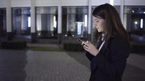 De jonge onderneemster met een smartphone loopt in een straat van de nachtstad, zijaanzicht stock video