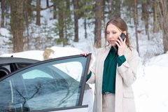De jonge onderneemster spreekt op een telefoon buiten haar auto stock foto's