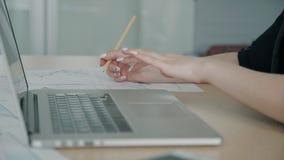 De jonge onderneemster werkt aan blauwdruk gebruikend laptop op bureau stock video