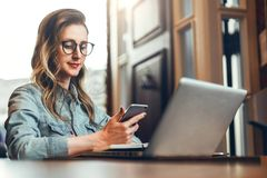 De jonge onderneemster zit in koffiewinkel bij lijst voor computer en notitieboekje, gebruikend smartphone Sociale Media stock afbeeldingen