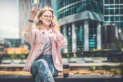 De jonge onderneemster zit op stadsstraat en spreekt op celtelefoon, omhoog opheffend haar hand Dichtbij is kop van koffie royalty-vrije stock afbeeldingen
