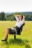 De jonge onderneemster zonnige weide ontspant op leunstoel Stock Afbeeldingen