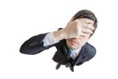 De jonge ongelukkige en beklemtoonde mens maakte fout en behandelt zijn gezicht met hand Geïsoleerdj op witte achtergrond Mening  stock afbeelding