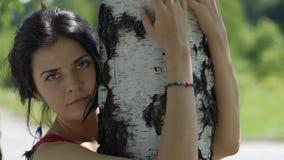 De jonge onschuldige vrouw kijkt in openlucht omhelzingen in camera een boom, liefde van aard, eenheid stock footage