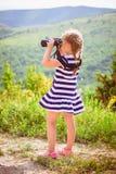 De jonge ontdekkingsreiziger bekijkt de toneelmening door verrekijkers Royalty-vrije Stock Fotografie