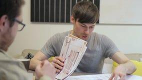 De jonge ontwerper bespreekt ontwerpproject binnen met klantenzitting in bureau stock video
